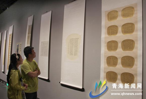 西宁市民明先生正在和女儿参观探讨青海省80后书法家二十人作品展,他