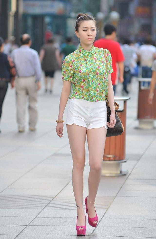 时尚街拍美女:白色短裤搭配花色短袖上衣的美女,一般人穿很难看,小姐