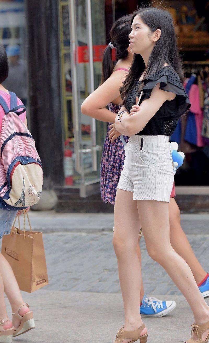 旅游景点街拍:竖条纹超短热裤搭黑色紧身上衣的长腿美眉,真漂亮