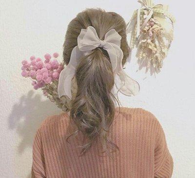 双马尾辫发型,烫卷的头发中分之后,以编发的方式聚集在耳后扎成低马尾