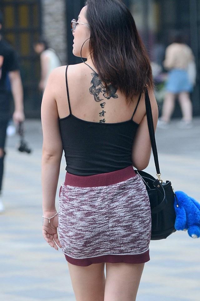 街拍: 露出背后文字纹身的美女, 只看清有一个字图片