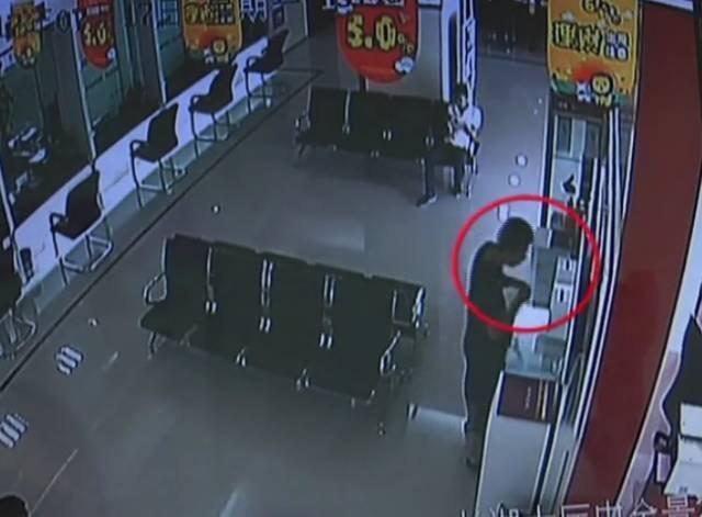 男子在银行里拿出一双筷子 夹取捐款箱内零钱
