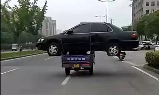 """男子800元买报废轿车 用三轮车""""驮""""着飞奔"""