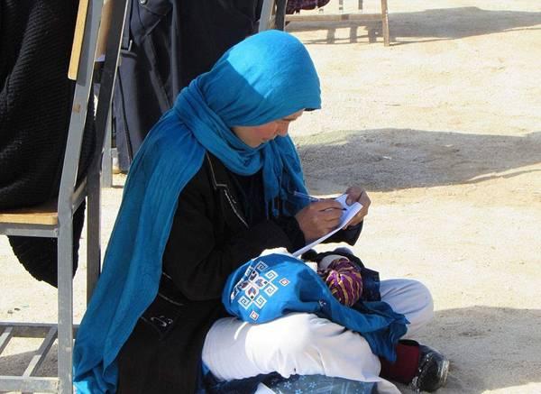 励志!阿富汗一母亲抱娃席地而坐参加大学入学考试